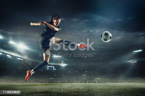 istock Female soccer player kicking ball at the stadium 1149530632