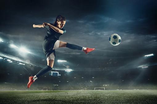 Female Soccer Player Kicking Ball At The Stadium — стоковые фотографии и другие картинки Атлет
