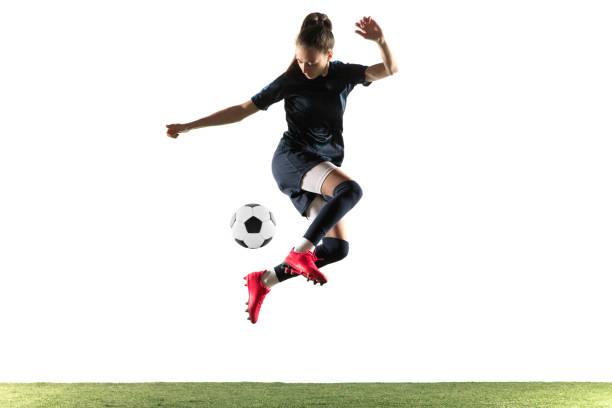 Weiblicher Fußballspieler kickt Ball isoliert über weißen Hintergrund – Foto