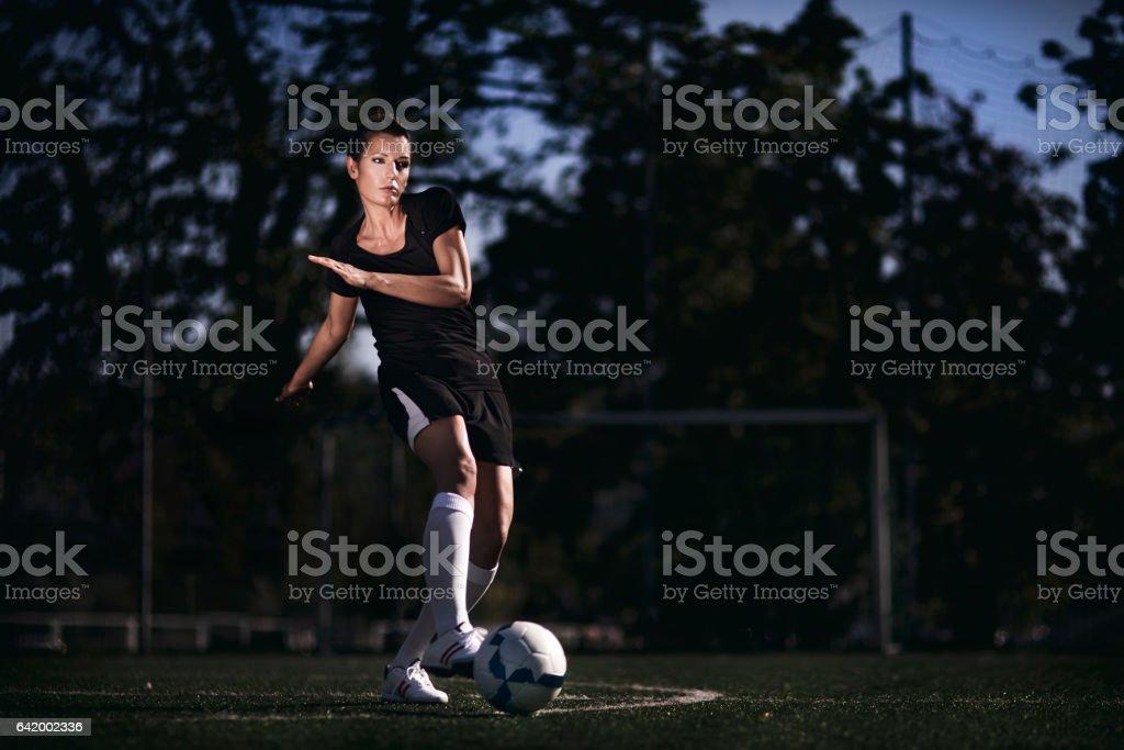 Female soccer player standing on soccer field, kicking ball.