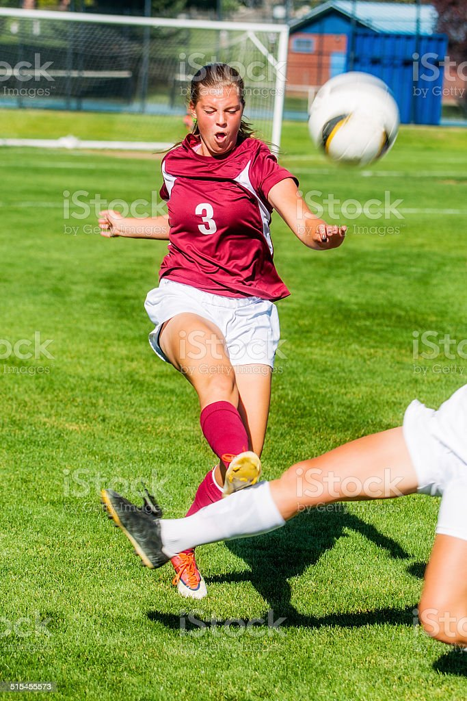 Female Soccer Player Kicks Ball While Under Heavy Challenge stock photo