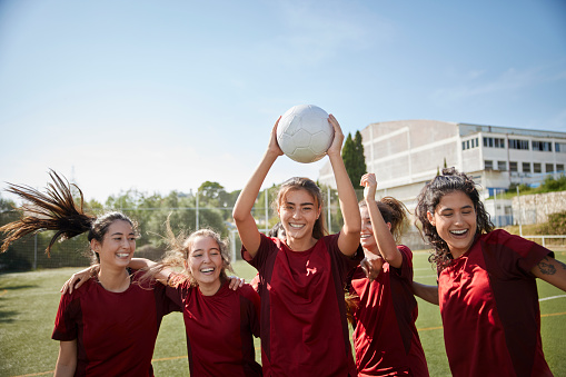 Female soccer player looking at camera celebrating goal with teammates in soccer field holding ball up