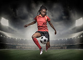 African Non-Caucasian Female Football Player controlling a Soccer Ball in front of Stadium Lights