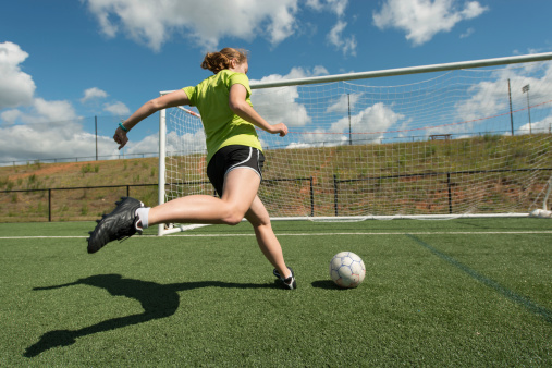 Young adult female soccer player practices shots on goal on a beautiful turf field