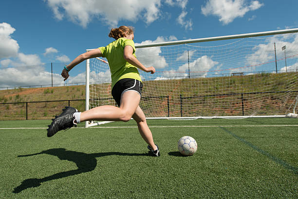 Female soccer player Young adult female soccer player practices shots on goal on a beautiful turf field female high school student stock pictures, royalty-free photos & images