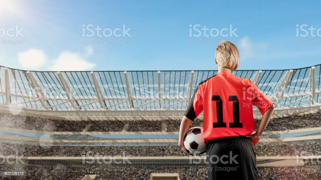 female soccer player standing with the ball against the crowded stadium on background stock photo