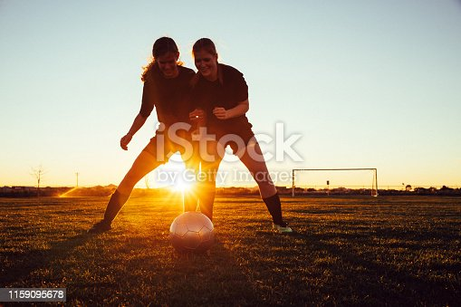 istock Female Soccer Players Battle for Ball 1159095678