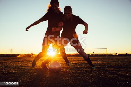 istock Female Soccer Players Battle for Ball 1159095689