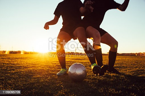 istock Female Soccer Players Battle for Ball 1159095709