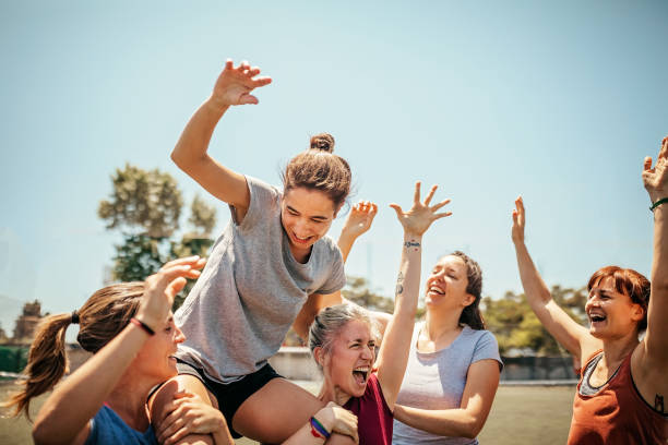 Female soccer players celebrating victory on soccer field stock photo