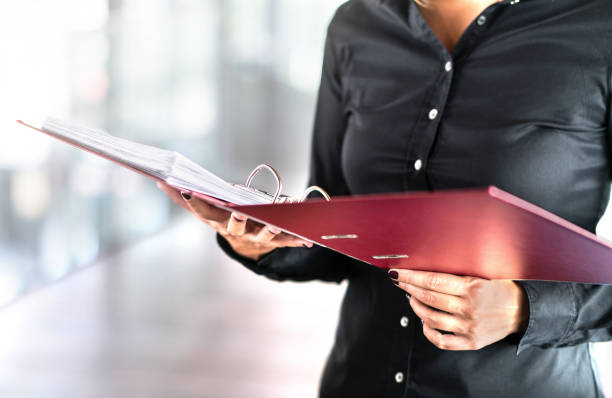 Female social worker, detective or business woman reading files in open folder. Accountant, investigator or adoption counselor. Volunteer in voluntary work. Female social worker, detective or business woman reading files in open folder. Accountant, investigator or adoption counselor. Volunteer in voluntary work. Successful person doing paperwork. ring binder stock pictures, royalty-free photos & images