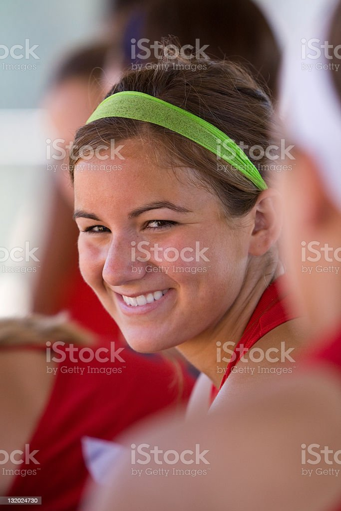 Female Softball Player Smiles In Dugout royalty-free stock photo