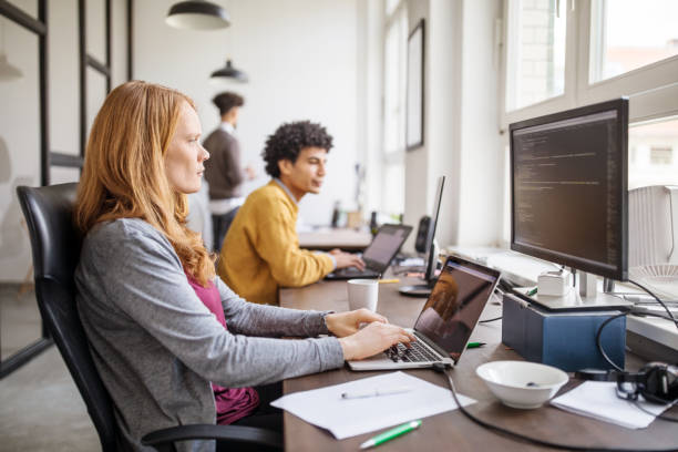 Female software programmer working with computers stock photo