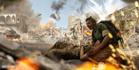 A female soldier medic wearing combat military uniform and backpack kneels on the ground and shouts for help whilst holding the head of an injured female colleague on her lap. The military personnel are both in a the middle of war zone amidst ruined buildings near explosions, smoke and fire.