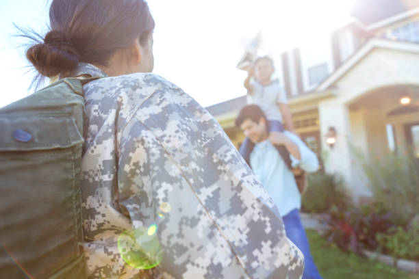 Female soldier returns home Rear view of mid adult female soldier returning home from military duty. Her husband and son are playing in the front yard. military lifestyle stock pictures, royalty-free photos & images