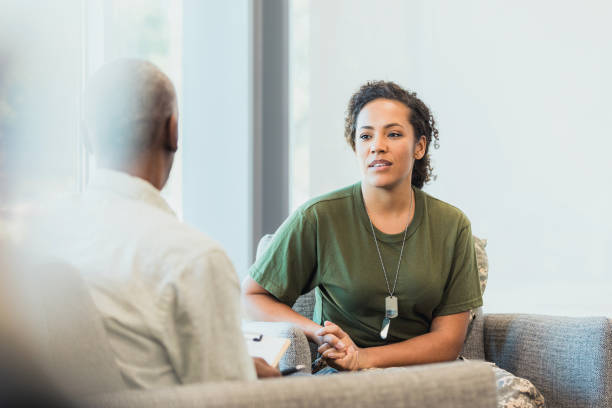 Female soldier talking with mental health professional stock photo