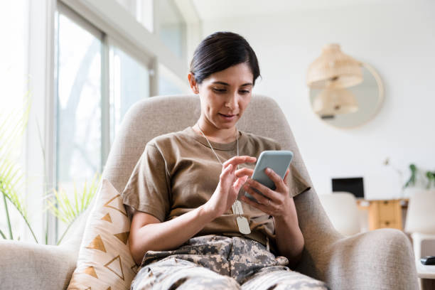 Female soldier texts while relaxing at home Mid adult female soldier concentrates while using a smartphone while relaxing in her home. military lifestyle stock pictures, royalty-free photos & images