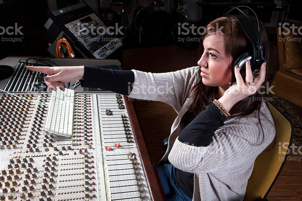 Female sound engineer at studio mixing desk stock photo