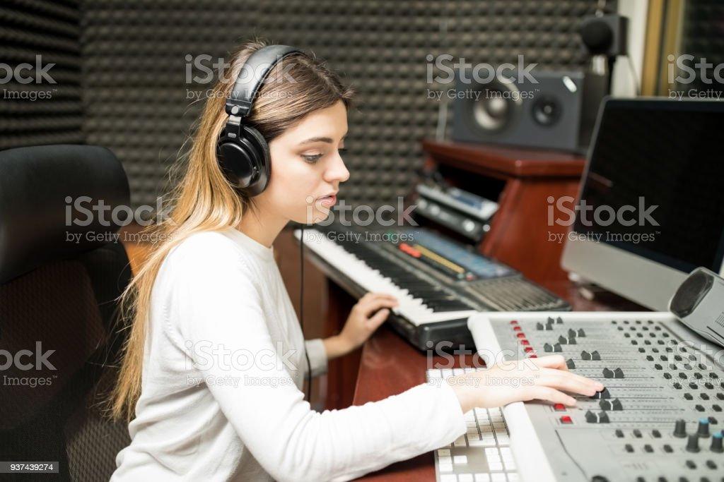 Female sound engineer composing music stock photo