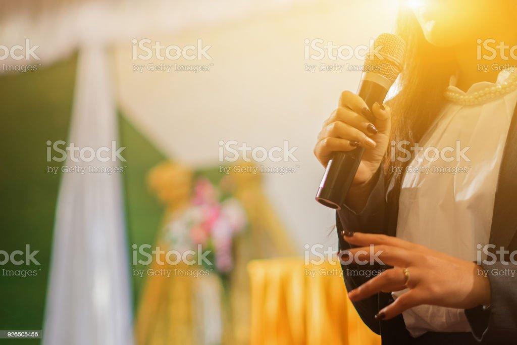 Maestro de altavoz femenino con presentación de micrófono al estudiante, niña usando un mic para cantar un song.vintage color enfoque selectivo - foto de stock