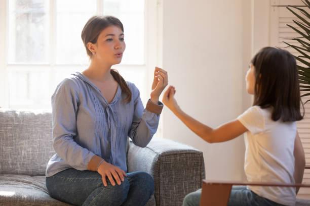 weibliche sprachtherapeutin, die bewegung macht, spricht mit einer kleinen patientin - lautbildungsspiele stock-fotos und bilder