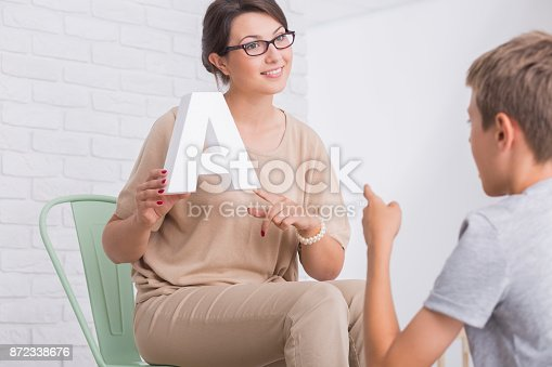 istock Female speech therapist showing letter 872338676