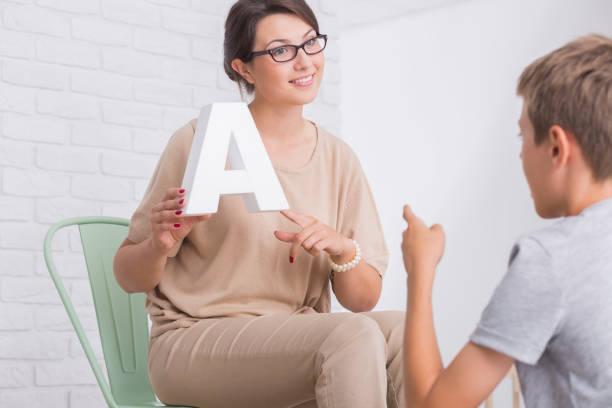 Female speech therapist showing letter stock photo