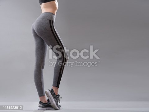 Female sportswear clothes on perfect body, Sneakers and grey leggings pants.