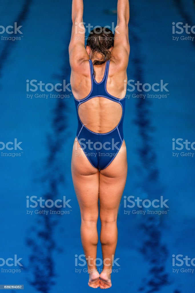 Female springboard diver in the air, high above the pool stock photo