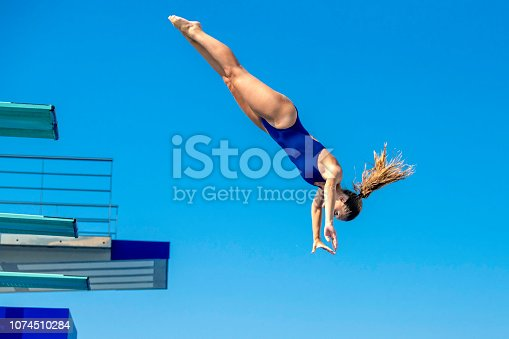 Low angle view of  a female springboard diver in mid-air, springboard and blue sky in backgrounds, copy space.