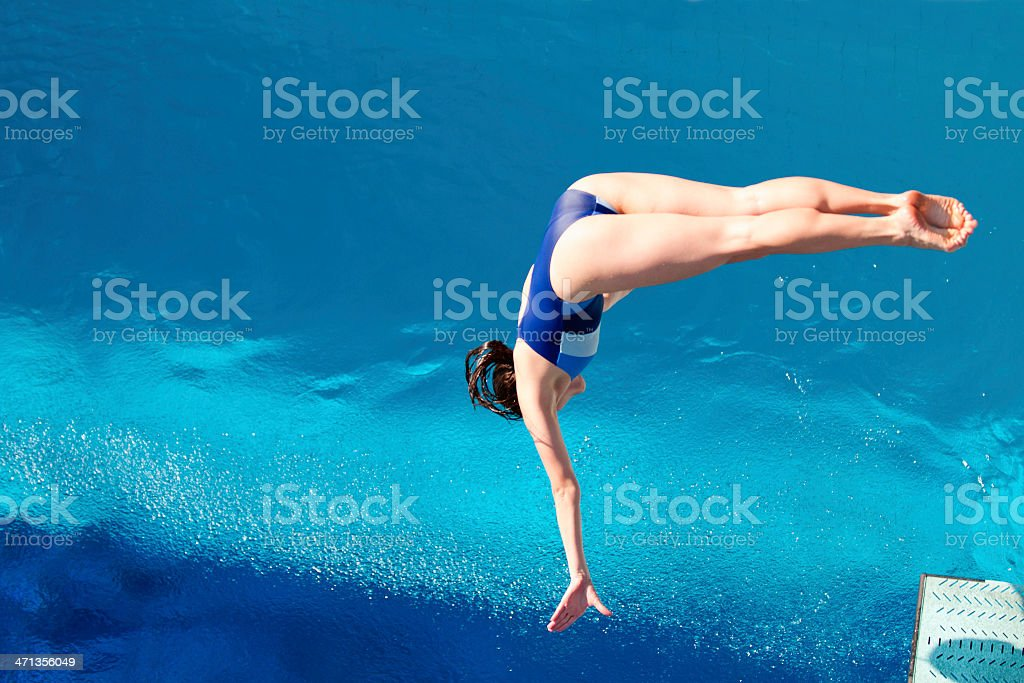 Female springboard diver takes off stock photo