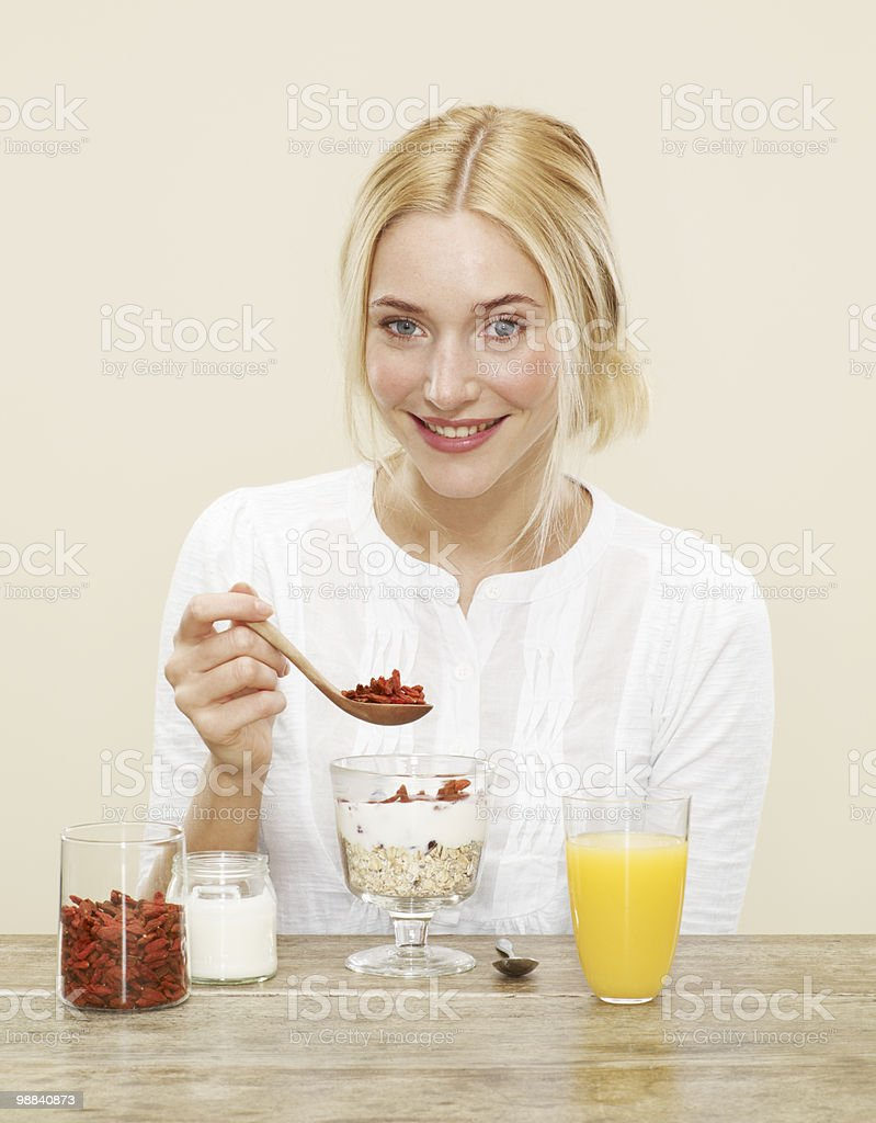 female sprinkling goji berries over her breakfast 免版稅 stock photo