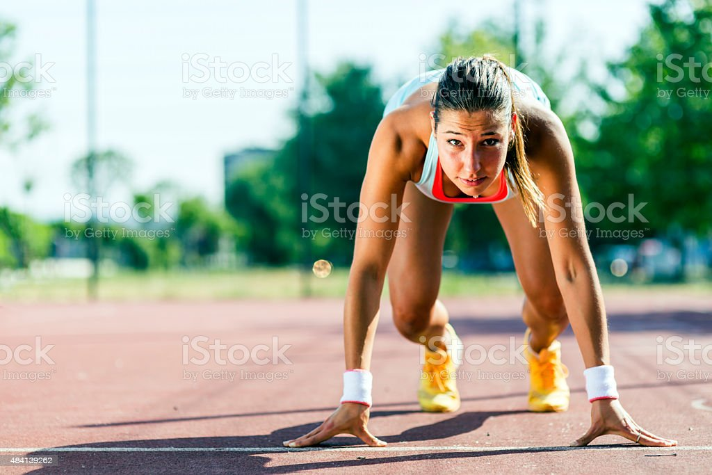 Female sprinter getting ready for the run stock photo