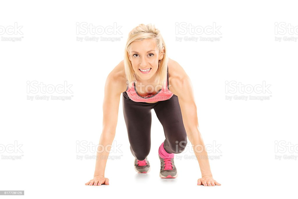 Female sprinter in starting position stock photo