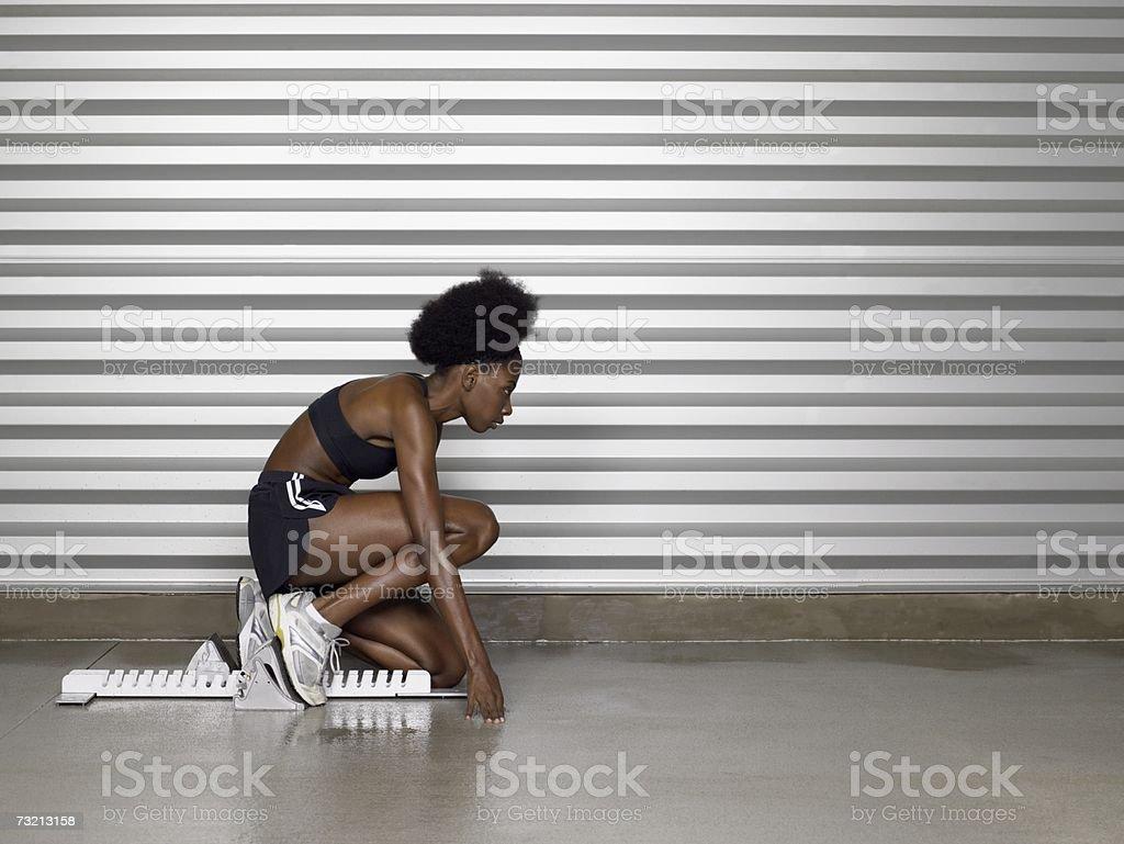 Female sprinter on starting blocks royalty-free stock photo