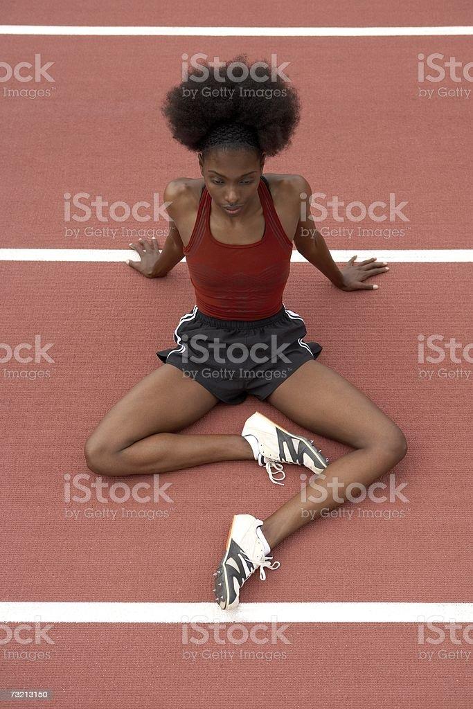 Velocista feminino alongamentos em uma Pista de Corrida foto de stock royalty-free