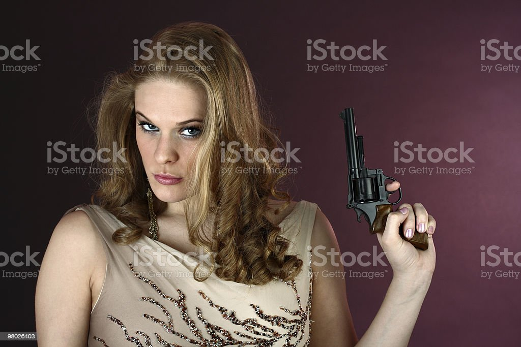 Female spy agent with gun pointing up on red background royalty-free stock photo