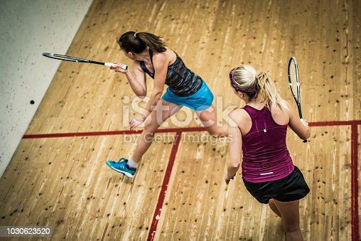 High angle view of a woman playing squash preparing to hit the ball.