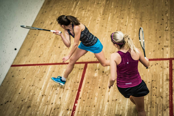 female squash player hitting the ball - racket sport stock pictures, royalty-free photos & images