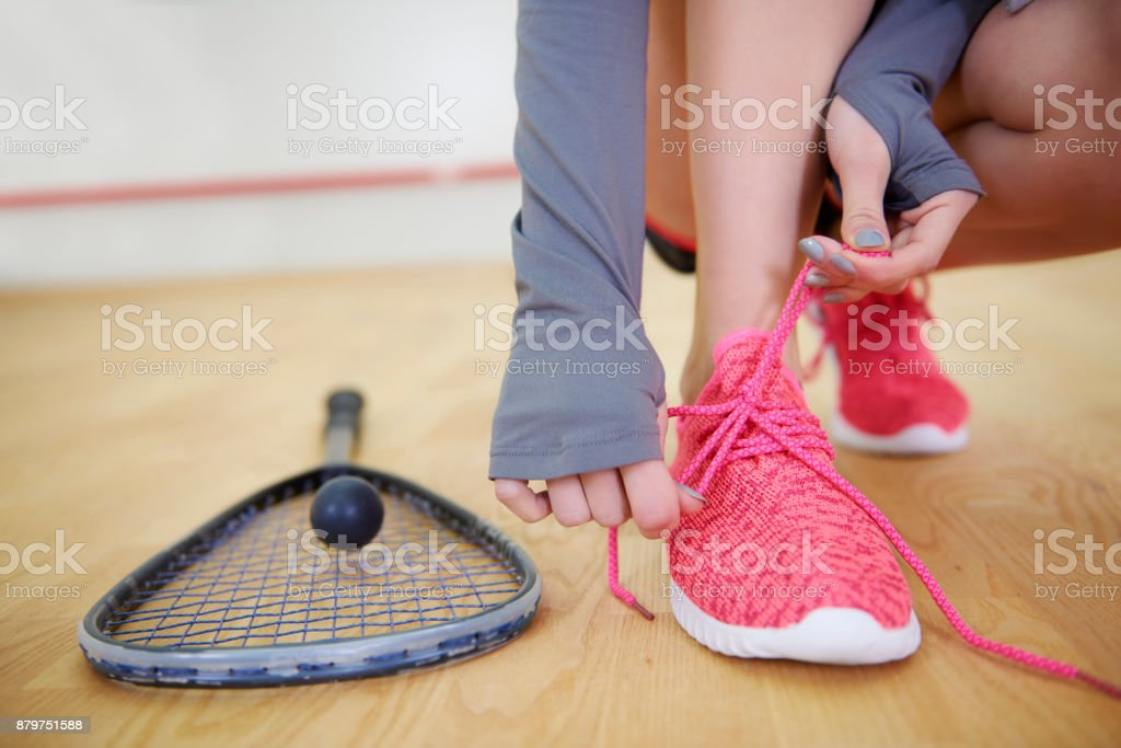 Female squash player tying sports shoe stock photo