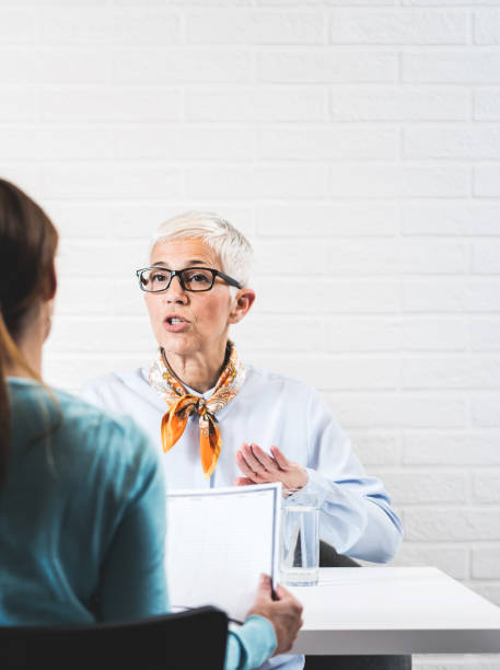 Female ssenior professor explains to the student about taking the exam stock photo