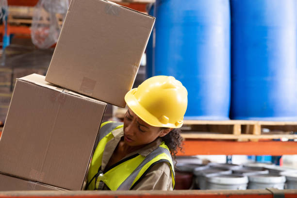 Female staff carrying cardboard boxes in warehouse stock photo