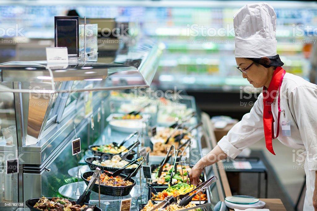 女性スタッフは、デリカテッセンのスーパーマーケット ストックフォト