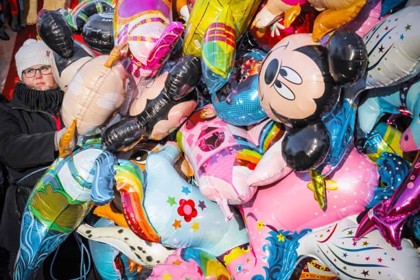 ein weibliches personal, schwebende ballons im winterwunderland weihnachten kirmes zu verkaufen - disney dekorationen stock-fotos und bilder