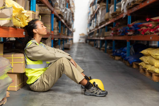 Female staff sitting with eyes closed in warehouse stock photo
