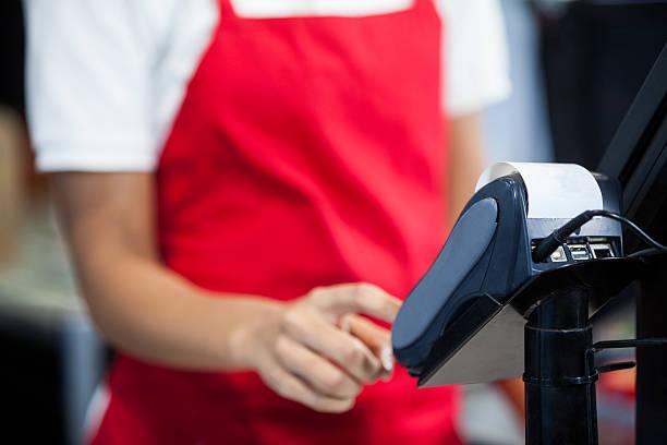 female staff using credit card terminal at cash counter - kassenbon stock-fotos und bilder