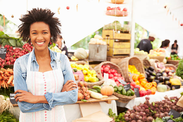 Female Stall Holder At Farmers Fresh Food Market stock photo