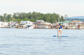 Female stand up paddleboarding on river