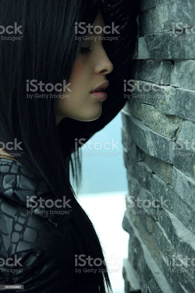 Female standing against a grey wall stock photo