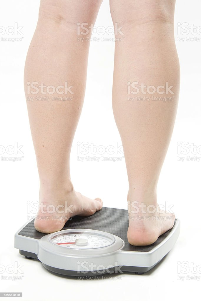 Female standing backwards on a scale royalty-free stock photo